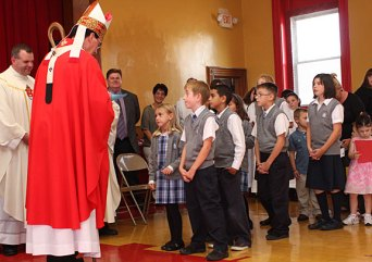 Archbishop Henry Mansell, left, accept gifts from St. Francis-Hedwig School students Allison Murphy and Justin Wilton during a ceremony blessing the new Naugatuck school Wednesday morning.