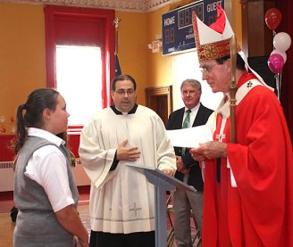 Archbishop Henry Mansell, right, accepts gifts from St. Francis-Hedwig School student Anna-Marie Allison during a ceremony blessing the new Naugatuck school Wednesday morning.