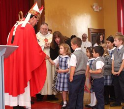 Archbishop Henry Mansell, left, accepts gifts from St. Francis-Hedwig School students Caitlin Dud and Aidan Leahy during a ceremony blessing the new Naugatuck school Wednesday morning.