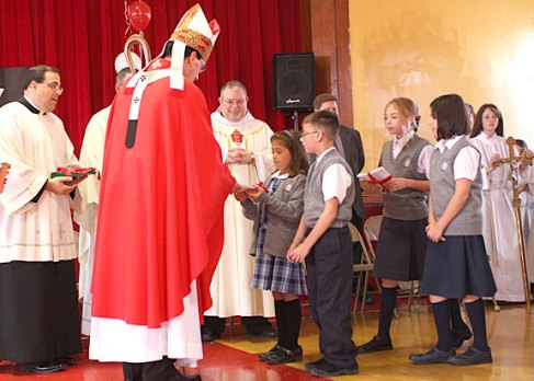 Archbishop Henry Mansell, left, accepts gifts from St. Francis-Hedwig School students Carina Cornacchia and Mike Marzano during a ceremony blessing the new Naugatuck school Wednesday morning.