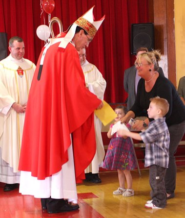 Archbishop Henry Mansell, left, accepts gifts from St. Francis-Hedwig School students Madison Mento and Ashton Morris, escorted by their teacher Carlene Russo during a ceremony blessing the new Naugatuck school Wednesday morning.