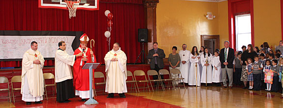 Archbishop Henry Mansell, center, flanked by, from left, Father Michael Slusz of St. Francis Church, Father Jeffrey Romans, secretary to the archbishop, and Father Kevin Forsyth, of St. Vincent Ferrer Church, speaks during a ceremony blessing the new Naugatuck school Wednesday morning.