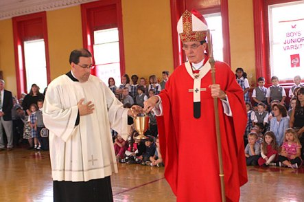 Archbishop Henry Mansell, right, followed by his secretary, Father Jeffrey Romans, blesses the new St. Francis-St. Hedwig school during a ceremony in the school gym Wednesday morning.