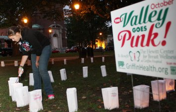 Dana Gridley lights a luminary during a ceremony Monday night on the Town Green to mark October as The Valley Goes Pink month.