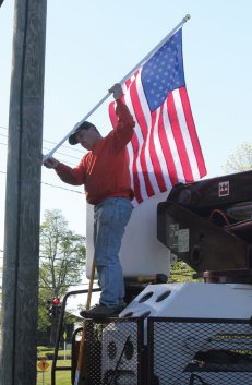 David Plante, a worker from Ed The Treeman, installs an American flag on a utility pole along Route 68 in Prospect May 12. The flag was one of 103 installed along the streets of downtown. Ed Brasche, owner of Ed The Treeman, donated five crews to put up the flags. The flags were purchased through donations to the Prospect Flag Fund, an initiative spearheaded by resident Robert Hiscox. –ELIO GUGLIOTTI