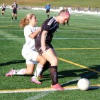 Taylor Campos, left, of Naugatuck tussles with Kelly Boucher of Woodland Nov. 5 in Watertown. The Greyhounds defeated the Hawks on penalty kicks to advance to the N VL championship game. –FILE PHOTO