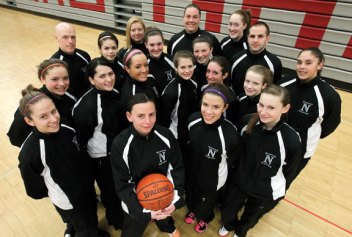 Naugatuck girls basketball head coach, Jodie Ruccio (center with ball) is surrounded by her coaches and team at Naugatuck High School. The team rallied around Ruccio, who lost her husband this past year.-RA ARCHIVE