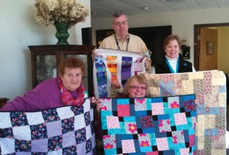 The Southford Falls Quilt Guild recently donated quilts to the Lutheran Home of Southbury recently. Pictured, from left, Charity Quilts co-chair Joann Macko, of Naugatuck, Lutheran Home administrator Tom Gaertner, Charity Quilts co-chair Doree Coy, and guild 1st Vice President Margaret Eng.