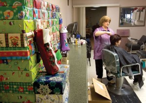 Dolly Lengyel, owner of Personal Pampering at 170 Church St. in Naugatuck, cuts hair among piles of gifts and supplies going to troops for the holidays in December. Every year, Lengyel collects and ships care packages to soldiers fighting overseas. For this, among other charitable activities, Lengyel was named Citizen of the Year by the Naugatuck Exchange Club. –RA ARCHIVE