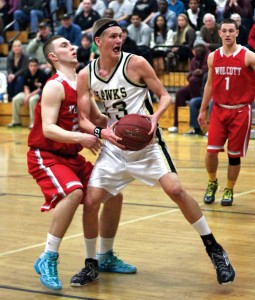 Woodland's Kirk Chamenko (13) backs down Wolcott's Nicholas Japs (20) before laying in a basket last Friday night in Beacon Falls. The Hawks soared past the Eagles, 86-73. –ELIO GUGLIOTTI