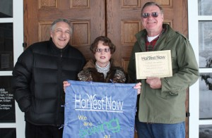 Harvest Now founder Brooks Sumberg, left, recognized Beacon Falls residents Ann and Fred Hopkins last Friday in front of St. Michael's Church in Beacon Falls. Harvest Now is a nonprofit organization that works to alleviate hunger by encouraging organizations to grow fresh food for those in need. Ann Hopkins has led the church's Harvest Now garden for the past two years. –ELIO GUGLIOTTI