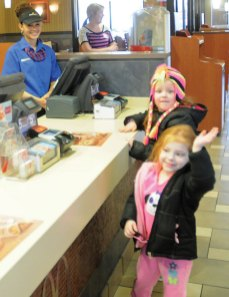 McDonald's employee Jenny Rodriguez looks on while Mallory Swindon, 4, waves and kindergartener Hannah Swindon, 5, wave to Hop Brook Elementary School first-grade teacher Jessica Frissora at the McDonald's on New Haven Road Feb. 21. Staff from Hop Brook worked at the restaurant for the Parent-School Association's McEducators night. A portion of the sales that evening went to the PSA. The organization raised $275.-LUKE MARSHALL