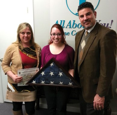 SPC Alicia Jordan, center, presents an American Flag that was flown over Salerno Hospital in Afghanistan during operation Enduring Freedom, to her employers All About You Home Care managing partners Yvonne Gamelin, left, and Rick Sales recently. Jordan presented the flag with a certificate of appreciation for care packages sent by All About You Home Care throughout her deployment. –CONTRIBUTED