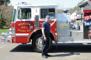 Beacon Falls firefighter and emergency medical technician Kurt Novak stands next to a 25-year-old fire engine at Beacon Hose Company No. 1 earlier this year. Money to buy a new fire truck to replace the engine pictured is one of three proposals voters will be asked to authorize on Tuesday night. –FILE PHOTO