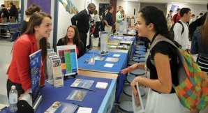 Jacqui Cohen, left, from Roger Williams University in Rhode Island, talks with Naugatuck High School senior Chelsy Lewis April 9 during college fair for juniors and seniors at the school. –LUKE MARSHALL