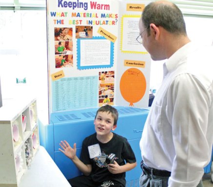 Algonquin School third-grader Logan Resnick, 9, discusses his science project on what material makes the best insulation with Dmitri Sonskoy April 11 during the school's 18th annual third-grade science fair. –ELIO GUGLIOTTI