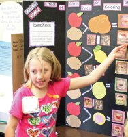Algonquin School third-grader Kaitlyn Sirois, 9, explains her project on the effect of citrus juice on the coloring of apples and potatoes to some of her younger classmates April 11 during the school's 18th annual third-grade science fair. –ELIO GUGLIOTTI