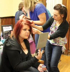 Jessica Marino of Sylvia's Colour & Design of Southbury puts a feather in the hair of Kaycie Brewer, of Beacon Falls, during the Girls Night Out event last year. This year's event will be held Friday from 6 to 9 p.m. at the Naugatuck Congregational Church and the ticket sales will benefit the Dawn Lafferty Hochsprung Memorial Fund.-FILE PHOTO