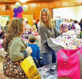 Chris O'Connell, right, of Thirty-One Totes in Oxford shows off one of her bags to Patricia Wasilewski of Naugatuck during the Girls Night Out April 5 at the Naugatuck Congregational Church. The event was hosted by Tender Years Preschool and raised $1,800 for the Dawn Lafferty Hochsprung Memorial Fund. –ELIO GUGLIOTTI