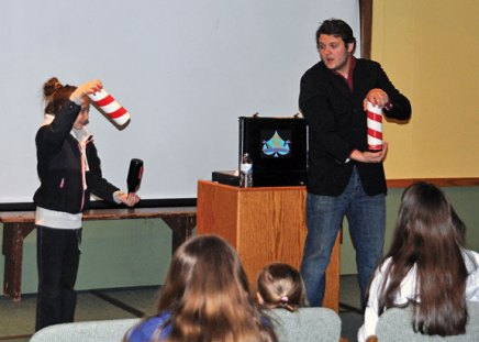 Olivia Loughlin, 11 of Naugatuck, assists magician Chris Lengyel with an illusion during a performance at the Whittemore Library in Naugatuck April 4. –LUKE MARSHALL