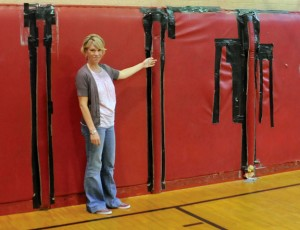 Naugatuck YMCA's dorm coordinator Lori Czajkowski points out the padding in the gym that is in bad shape. The state Bond Commission has approved a $317,500 grant for the YMCA to help pay for renovations, including replacing the padding. –LUKE MARSHALL