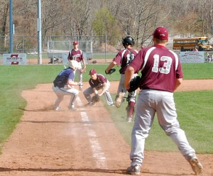 Adam Thayer of Ansonia is caught in a rundown between third base and home as Naugatuck's Matt Bradley closes in for the tag as Naugatuck catcher John Dean and pitcher Adam Tavares (13) back him up April 26 at Rotary Field in Naugatuck. Ansonia won the game, 9-1. –KEN MORSE