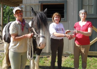 Holly Bucalos, a representative from Athelas Therapeutic Riding of Otego, N.Y., right, presents Hidden Acres Therapeutic Riding Center board member Debbie Morrow with a $500 donation June 1 at the center in Naugatuck as Hidden Acres Program Director and horse Kendall look on. The donation is for Hidden Acres to serve a participant from Newtown, who has been affected by the December shooting at Sandy Hook Elementary School. Bucalos reached out to Pellino and began raising funds to help provide support for the participation of an individual from the Newtown area affected by the tragedy. Kendall was also donated to the program in hopes she would bring joy and emotional healing to those impacted by trauma. Hidden Acres is reaching out to the Newtown community in hopes of encouraging an individual that may benefit from equine-assisted activities to contact the center. Their participation in the upcoming semester would be supported through the donation. For more information, contact Hidden Acres Therapeutic Riding Center at (203) 723-0633 or hiddenacres2@gmail.com or visit www.hiddenacrestrc.org. -CONTRIBUTED
