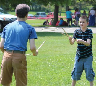 Algonquin School third-grader Tyler Macdowall, right, plays graces with Chris Lynch, 14, of Prospect on the Town Green. Third-graders from the school in Prospect stepped back in time to learn about the town and its history. The students toured Town Hall, Prospect Cemetery, the Center One schoolhouse and the Hotchkiss House and barn. As part of the day, students wrote with quill pens and played games from yesteryear. The program was organized by third-grade teachers Marcia Beltrami, Elena Guerra and Kathleen Bicio and the Prospect Historical Society. The program was funded through the Region 16 innovative grant initiative. The program ties into the state's social studies standards and the students will be creating a history book about Prospect for children. –ELIO GUGLIOTTI