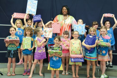 Girls Scouts from Daisy Troop 65439 of Prospect pose for a picture with Deborah Pierce, program recruiter of New Opportunities, Inc. in Waterbury, as they hold toys they donated for the organization's toy drive. In celebration of Isabella LaMaine's (front center) seventh birthday she invited her Daisy Troop to donate a gift for the New Opportunities toy drive. Pierce came to the last Daisy meeting of the year to accept the gifts and to talk with the girls about her organization. –CONTRIBUTED