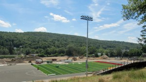 Constructions workers lay down the new artificial turf field at Naugatuck High School Monday afternoon. –KYLE BRENNAN