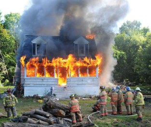 Firefighters from the Volunteer Fire Department of Prospect watch as a house at 122 Waterbury Road in Prospect is engulfed in flames during a live burn demonstration on Sunday. The department performed training exercises at the vacant home over the weekend. –LUKE MARSHALL