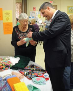 The Naugatuck Senior Center and the Naugatuck Savings Bank Foundation presented the annual Naugatuck Valley Senior Day Sept. 19 at the senior center on Meadow Street. The event featured over 40 informational booths. Senior center member Dorothy Gouveia, left, shows off some of the items her and other members crotched to Naugatuck Mayor Robert Mezzo. –LUKE MARSHALL