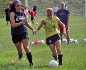 Woodland sophomore Jess Rodrigues dribbles past senior captain Andrea Piccolo during practice Sept. 3 as new coach Cait Witham looks on. –KYLE BRENNAN