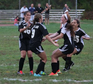 Woodland's Gillian Hotchkiss (16), Shae Geary (9), Audra Blewitt (4) and Maribella Sousa (25) celebrate after Geary scored on a penalty kick versus Naugatuck Sept. 13 at Breen Field in Naugatuck. –ELIO GUGLIOTTI