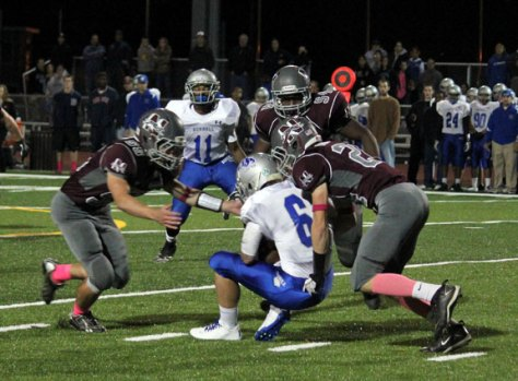 Naugatuck's Patrick Murphy (55), Socrates Illunga (54) and Bryan Burke (24) smother Bunnell quarterback Nolan Aurelia (6) in the backfield Oct. 18 in Naugatuck. The Greyhounds dominated Bunnell, shutting out the Bulldogs and holding them to 105 total yards of offense. –ELIO GUGLIOTTI