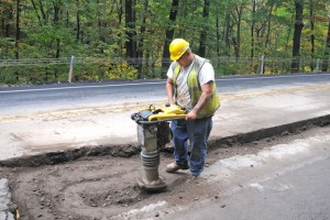 Bobby Vitale of Henkels & McCoy uses a jumping jack tamper to pack the dirt back down after a section of gas pipe was laid along Route 69 in Prospect Monday. -LUKE MARSHALL