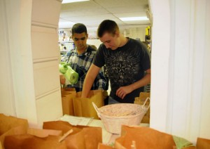 Naugatuck High School students Vinny DeCastro, 18, left, and Derek Ritter, 19, help pack grocery bags at the Naugatuck Ecumenical Food Bank on Nov. 8. The food bank is seeking donations as the holidays approach and the numbers of those who need the service has grown. –LUKE MARSHALL