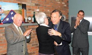 "Beacon Falls First Selectman Christopher Bielik hugs Lt. Gov. Nancy Wyman after being sworn in Nov. 15 at the home of John ""Jack"" Betkoski III IN Beacon Falls as state Sen. Joseph Crisco (D-17),left, and Selectman Peter Betkoski applaud. –LUKE MARSHALL"