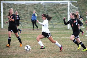 Woodland's Marisa Macek (15) brings the ball up field between Plainfield's Sarah Pric (12) and Hannah Robillard (6) Nov. 6 during the second round of the Class M state tournament in Beacon Falls. The Hawks rallied to beat Plainfield, 2-1, but couldn't repeat the feat Nov. 8 in the quarterfinals versus Weston. The Trojans defeated the Hawks, 2-1. -LUKE MARSHALL