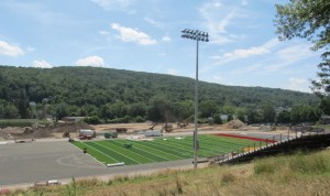 Workers layout the new Veterans Field turf this summer at Naugatuck High School. –KYLE BRENNAN