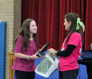 Britany Sweet, right, an intern at Community School in Prospect, presents fifth-grader Abby Colt with a Kindle Dec. 20 for raising the most money during Region 16's Read-A-Thon for Brianna. Colt raised $612. –ELIO GUGLIOTTI