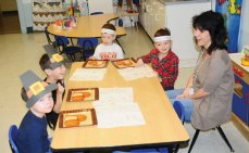 Naugatuck YMCA preschool students, from left, Wesley Wergin, 4, of Naugatuck, Vincenzo Caminita, 4, of Naugatuck, Adam Hayward, 4, of Naugatuck, and Maximus Lapke, 4, of Middlebury sit with their teacher Andrea Rodgers at the YMCA Nov. 27 for a Thanksgiving meal. The students each made a Pilgrim hat and a Native American headband to wear during the meal. –LUKE MARSHALL