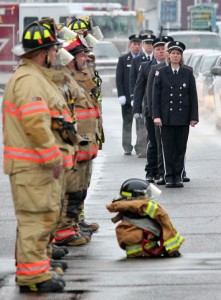 The firefighting gear of the late Roger Brennan, a former fire chief of Beacon Hose Company No. 1, is laid out on the sidewalk in front of the firehouse on North Main Street in Beacon Falls as firefighters stand at attention Jan. 27 during Brennan's funeral procession. –ELIO GUGLIOTTI