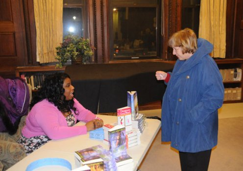 "Author Ginger Jamison, who also writes under the name Sugar Jamison, left, talks with Eugenie Cody, of Naugatuck, Feb. 12 at the Whittemore Library in Naugatuck. Jamison and seven other local romance authors were at the library for its ""Ladies' Night Out!"" event. The authors read from their novels, talked with audience members and signed copies of their books. –LUKE MARSHALL"