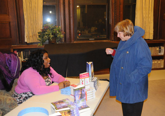 """Author Ginger Jamison, who also writes under the name Sugar Jamison, left, talks with Eugenie Cody, of Naugatuck, Feb. 12 at the Whittemore Library in Naugatuck. Jamison and seven other local romance authors were at the library for its """"Ladies' Night Out!"""" event. The authors read from their novels, talked with audience members and signed copies of their books. –LUKE MARSHALL"""