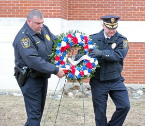 Naugatuck police Lt. Bryan Cammarata, left, and Deputy Police Chief Josh Bernegger carry a wreath to lay at the foot of the flag pole in front of the Naugatuck Police Department Monday morning during a brief ceremony to mark the 23rd anniversary of the death of borough police Officer Nancy Nichols. Nichols was killed March 17, 1991, when she was struck by a car after stopping to help a fellow officer. –ELIO GUGLIOTTI