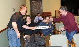 Mark Szamatulski, left, gives a sample of homemade beer to, from left, Naugatuck residents Gary Stockings, Ryan Armiento and Ken Armiento during a craft beer making and tasting event at the Whittemore Library in Naugatuck March 5. Mark and Tess Szamatulski, who own Maltose Express, a home brewing and wine making supply store in Monroe, came to the library to give a class on making beer. –LUKE MARSHALL