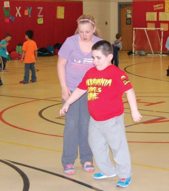 Maple Hill School first-grader Odin Anderson receives some help during a drill from volunteer Alyssa Roberts, a fifth-grade student at Cross Street Intermediate School, during the Hoops and Homework program at the school in Naugatuck April 8. The program, which Ruccio developed, is designed to help the first- through fourth-graders at Maple Hill School to become better at basketball while enforcing good study habits by being successful in their homework assignments. –KEN MORSE