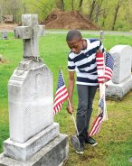 City Hill Middle School seventh-grader Floyd Labbe places a flag on the grave of a veteran at St. James Cemetery May 15. City Hill students assisted brothers Bill and Manny Matos to put flags on the graves of veterans in preparation for Memorial Day. –LUKE MARSHALL