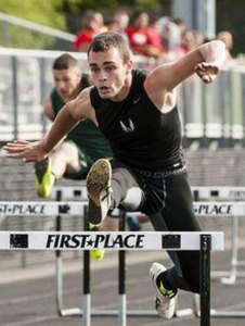 Woodland's Mike Lang clears a hurdle on his way to a first-place finish. The Woodland boys and girls teams beat Holy Cross, St. Paul and Derby to claim the NVL titles. –RA ARCHIVE